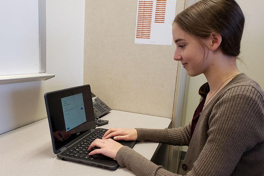 Freshman Anna Yates works on a Chromebook