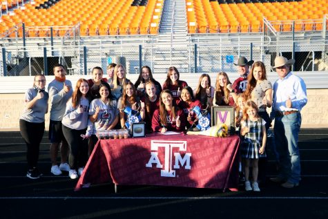 Senior Mattie Gustin posing with family, friends, and coaches after she signed to Texas A and M.