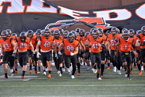 Varsity football team runs onto the field against Cedar Hill on Oct. 17.