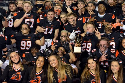 Football players and cheerleaders pose with the BI-District game trophy on Dec. 12.