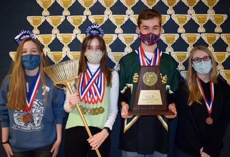 The UIL Journalism Team (right to left) senior Lydia Wood, senior Olivia Caggiano, senior James Ward and freshman Cassidy Cole pose outside the journalism room with their first place trophy.