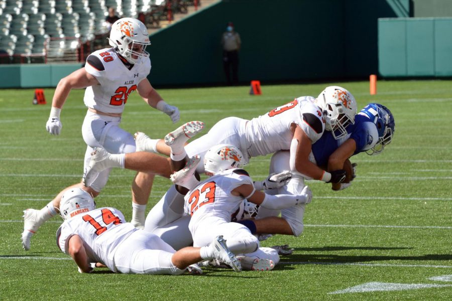 Senior cornerback Blake Walter, #14, senior linebacker Sam Forman, #20, senior safety Elijah Valencia, #23, and  junior defensive end Kyle Thompson, #43, tackle a Weatherford receiver Sept. 26. The Bearcats defeated the Roos 70-7 at Globe Life Field.