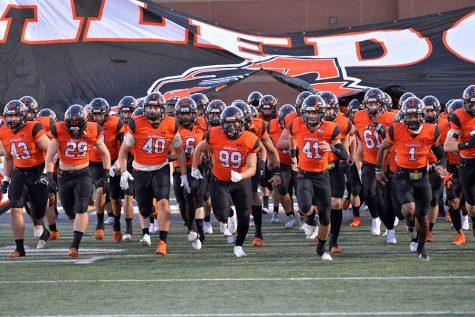 The varsity football team running onto the field against Cedar Hill on Oct.16