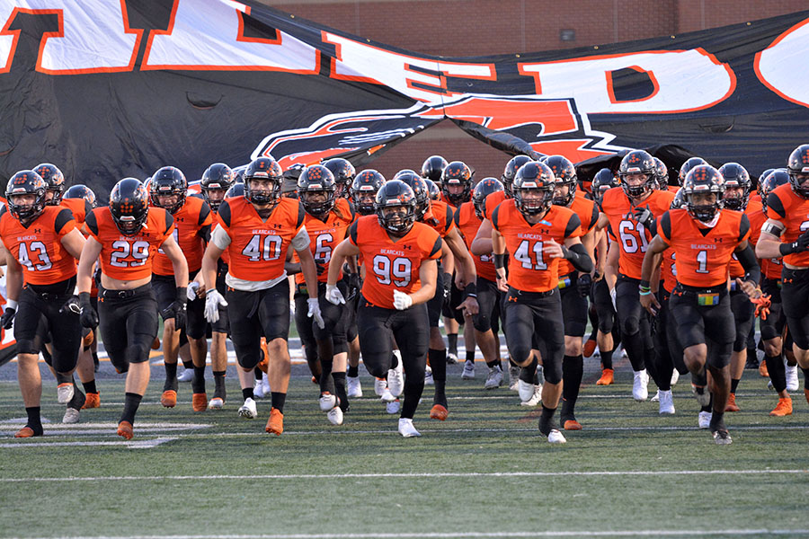The varsity football team running onto the field against Cedar Hill on Oct.16