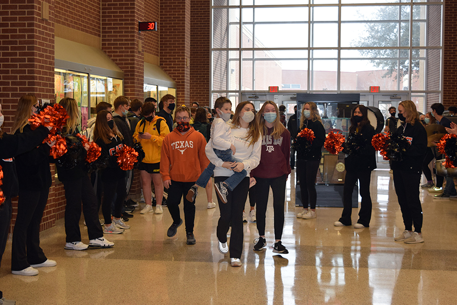 Madi McDonald and Ava Willis walk through the hallway during the state swim send off on Mon. March 1.