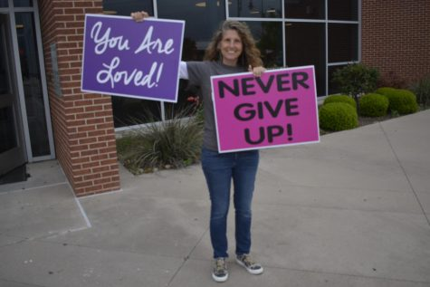 Volunteers hold signs of encouragement for students