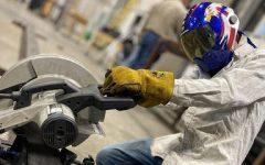 Junior Corbin Haber uses a circular saw to cut through steel.