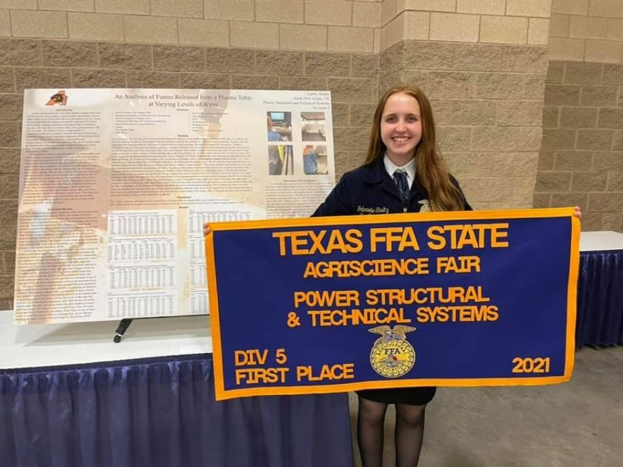 Senior Gabby Shultz holds her first place banner at the Agriscience Fair.